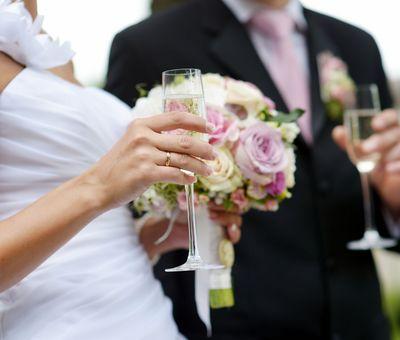 Hochzeitspaar mit Sektglas und Brautstrauß