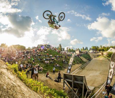 Im Hintergrund sind die Zuschauer, im Vordergrund ein Biker der Stunts in der Luft macht