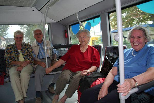 Vier aeltere Menschen sitzen im Bus