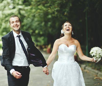 Hochzeitspaar lachend auf einem Waldweg