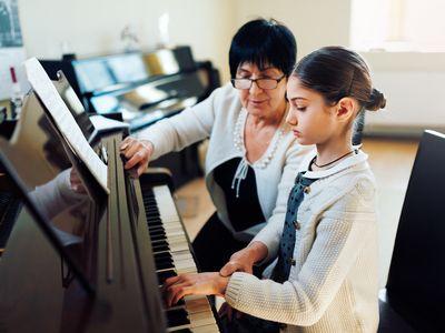 Ein Mädchen bekommt Klavierunterricht