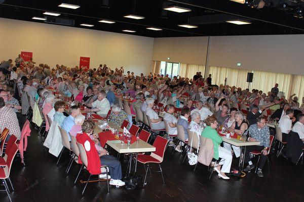 Viele Senioren sitzen an den Tischen und schauen gespannt dem Programm des Seniorentages zu
