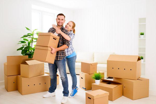 Es stehen viele Kartons in einem Raum und ein Paar hält zwei Kartons in der Hand.
