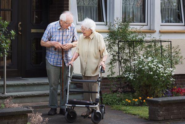 Ein Senior und eine Seniorin mit einem Rollator