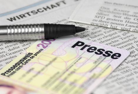 Auf verschiedenen Zeitungen liegt ein Kugelschreiber.