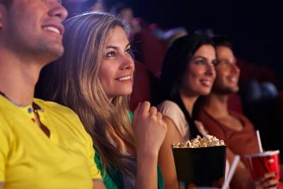 Eine Frau sitzt im Kino und isst Popcorn