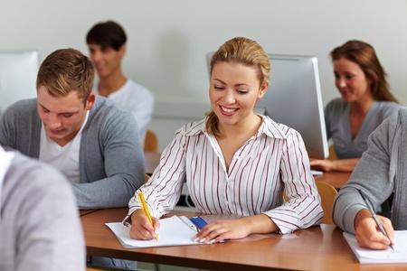 Junge Menschen sitzen an Schreibtischen