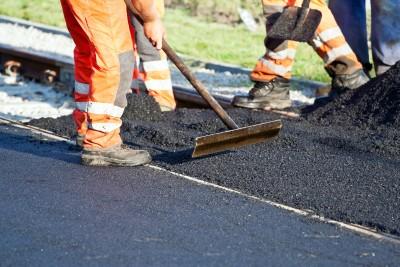 Bauarbeiter bringen eine Teerschicht auf einer Straße auf